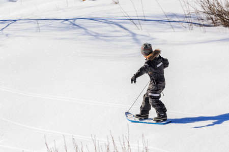 coatee: Child boy playing with their toys in a snowy slope on a bright winter day