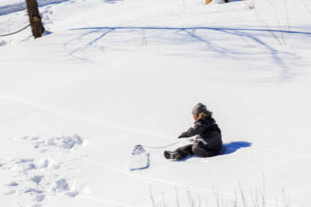 tog: Child boy playing with their toys in a snowy slope on a bright winter day