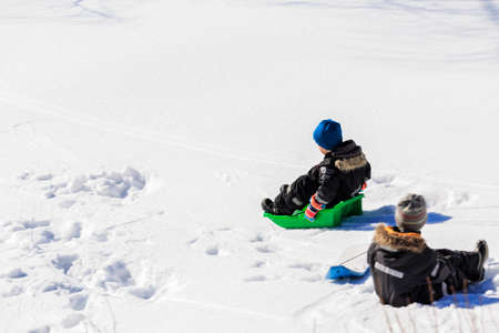 to go sledding: Child boy playing with their toys in a snowy slope on a bright winter day