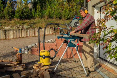 tog: Adult man sawing boards outside a garage