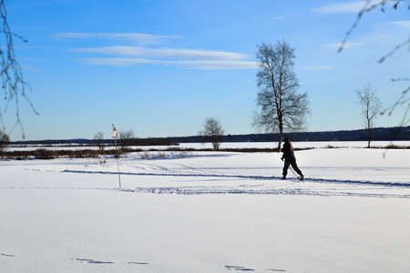solstice: Woman cross country skiing in late winter with a low solstice