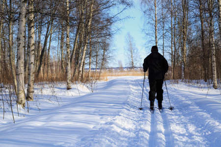 tog: Woman cross country skiing in late winter with a low solstice