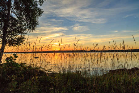 mirk: Scenic view over lake surface at sunset Stock Photo
