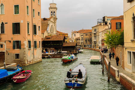 humilde: Venice, Italy – September 25, 2015: Skippers and other people on their way to different tasks they have an afternoon at the canal in Venice
