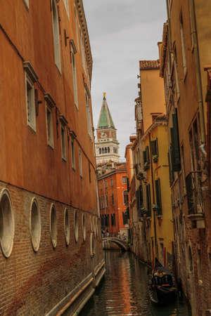 humilde: Venecia, Italia - 25 de septiembre de 2015: Una g�ndola ancl� en un estrecho canal de una tarde con campanario de San Marcos en el fondo Editorial