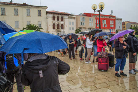rainwear: Porec, Croatia – September 23, 2015: Tourists queuing in Porec for the boat transport over the Adriatic sea to Venice in Italy Editorial