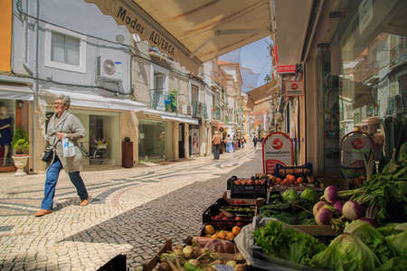 coatee: Setubal, Portugal - April 8 2016: Adult lady walking in the old part of the City of Setubal in an afternoon