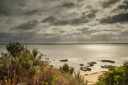 mirk: Troia peninsula with the Sado river under heavy dark clouds in the sunset