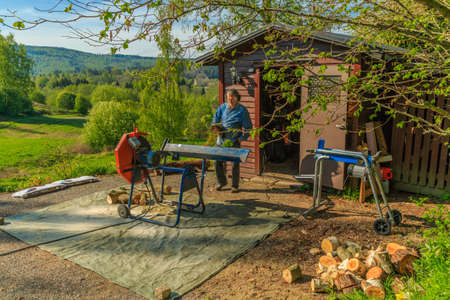 tog: Cutting and cleaving logs a afternoon in a sunny summers day Stock Photo
