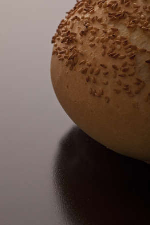 roasted sesame: Closeup of the edge of a golden crisp crusty roll with roasted sesame seed on a dark background with copyspace Stock Photo