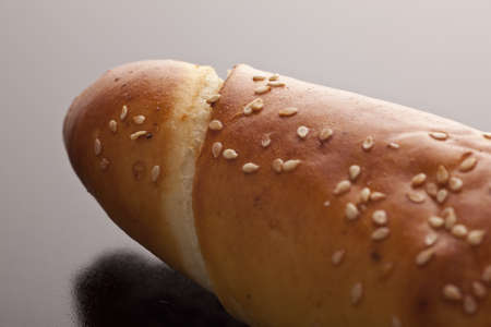 accompaniment: Closeup of the end of a crisp crunchy fresh baguette with sesame seed for a delicious accompaniment to a meal