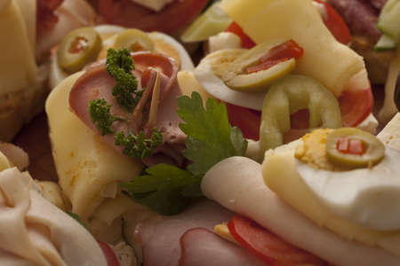 Closeup of delicious appetizers at an event with cheese, ham and sliced olives