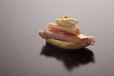 Delicious open ham and cheese sandwich stacked high on white bread for a tasty start to a meal or as a snack Stock Photo - 17597388