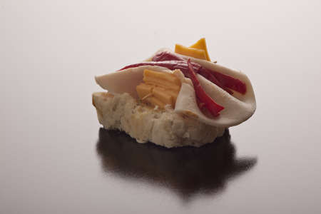 Tasty ham, pimento and cheese appetiser on sliced baguette against a dark reflective studio background with copyspace