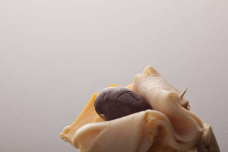 Closeup view of thinly sliced ham, olive and cheese on bread over a neutral studio background with large copyspace