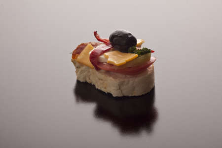 Tasty cheese snack on sliced baguette topped with a black olive on a grey background with copyspace