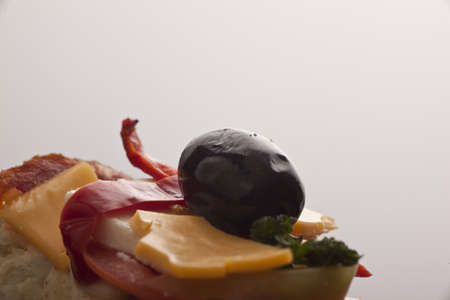 Closeup of a large black olive with cheese and pimento on salami against a neutral studio background