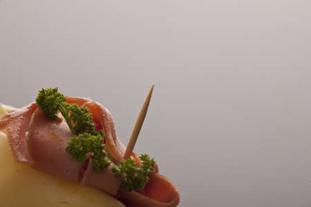 Ham and parsley topping on an appetizer against a grey studio background with copyspace