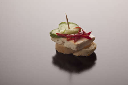 Feta cheese, pimento and gherkin on a baguette slice on a reflective studio background with copyspace