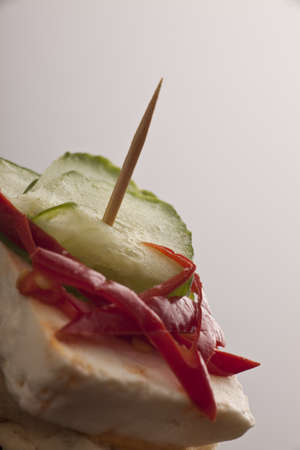 Feta cheese with pimento and gherkin slices served as a snack at a catered event against a neutral studio background