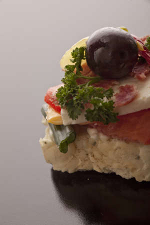 nutritive: Closeup of a tasty appetizer with feta, tomato and olive garnished with parsley