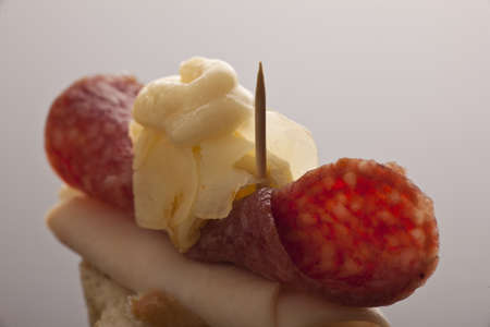 flaked: Thinly sliced salami and ham with mayonnaise served with flaked cheese on a sliced baguette as a starter at a catered event