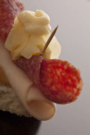 flaked: Closeup of a single salami and ham hors doeuvre topped with flaked cheese and mayonnaise with copyspace