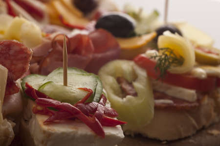 Variety of delicious appetizers on a buffet featuring different cheeses and meats with shallow dof Stock Photo