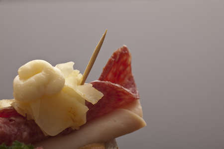 flaked: Closeup of a toothpick piercing thinly sliced rolled salami and ham topped with flaked cheese and mayonnaise in a tasty starter with copyspace