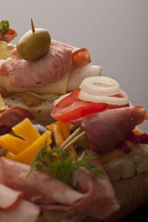 Assortment of appetizers with a variety of different meat toppings displayed on a buffet at a catered event or function