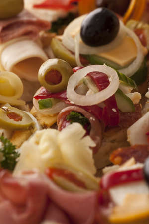 Closeup view of a plate of closely packed delicious appetizers with various cheeses, olives and cold meats on a buffet at a catered event