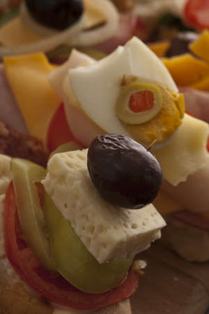 Closeup of appetizers on a buffet with feta cheese, hard-boiled egg and colourful cheddar combinations on fresh crusty sliced baguette Stock Photo