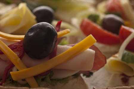 Appetizer selection at an event with tasty cheese, meat, lettuce, tomato and olive combinations with shallow dof