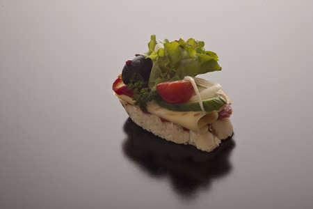Sliced baguette with cheese topped with fresh salad ingredients on a dark background with copyspace
