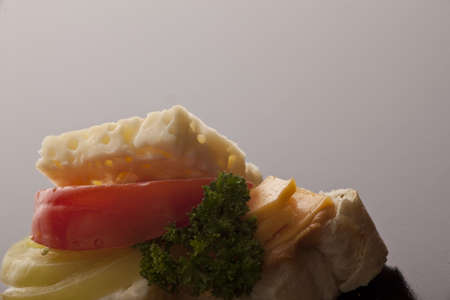 Slice of fresh crusty baguette with cheddar and feta cheese, tomato and olive on a dark background with copyspace