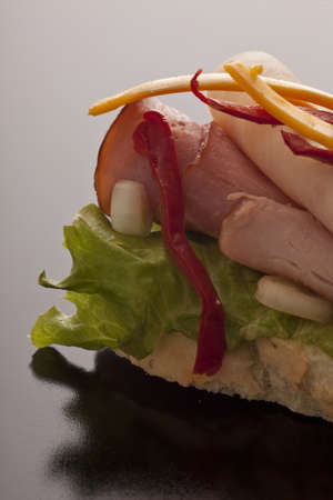 thinly: Open sandwich on crusty sliced white bread with thinly sliced ham and lettuce, closeup on a dark background Stock Photo