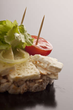 Closeup of portions of delicious feta cheese with cherry tomato and lettuce on a rice cake