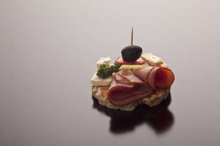 thinly: Delicious thinly sliced rolled ham and feta appetiser on a crisp rice cake topped with tomato and a black olive