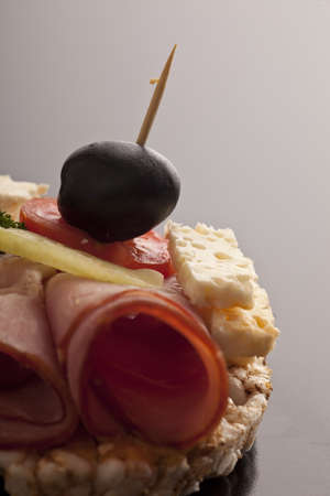 Delicous rice cake snack with thinly sliced rolled ham, feta cheese, tomato and a black olive served as a starter at a function