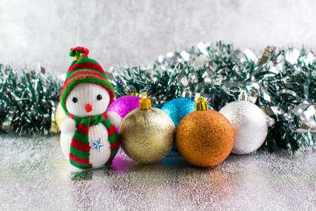 Palle di Natale e pupazzo di neve su uno sfondo d'argento.