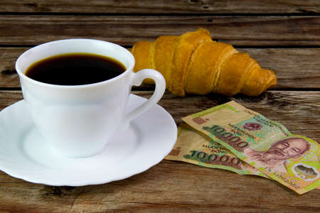 White cup of black coffee, croissant and Vietnamese money. Stock Photo