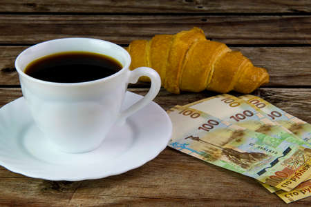 White cup of black coffee, croissant and rubles.