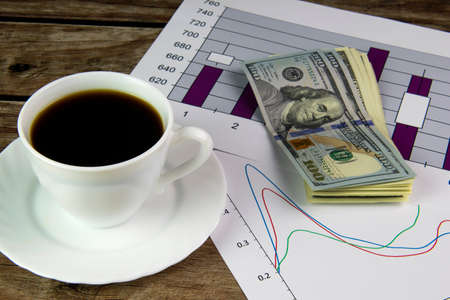 White cup of black coffee, graphics and dollars.