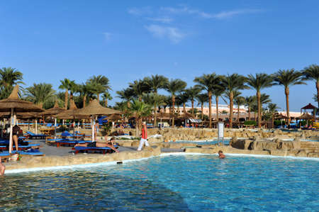 HURGHADA, EGYPT - OCTOBER 14, 2013:Unidentified people swim and sunbathe in the swimming pool at a luxury tropical resort in Egypt. Hurghada, Egypt Editorial
