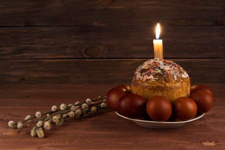 Easter cake, Easter eggs and a lighted candle on a wooden table Фото со стока