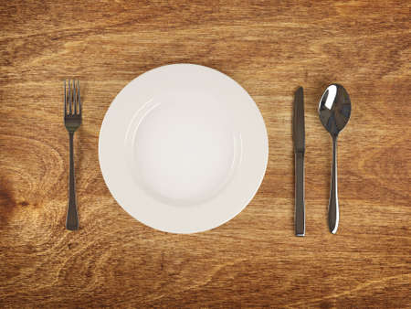 Plate and silver flatware on wooden table