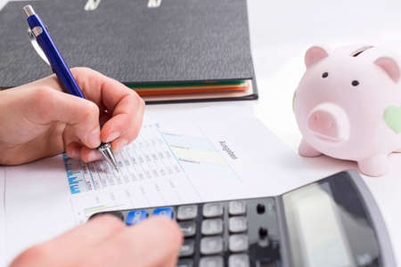 Women calculate expenses with calculator and piggybank
