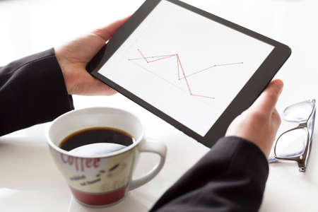 Hands with tablet and coffee analyzing diagram photo
