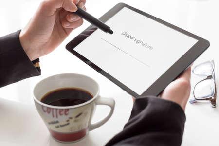 タブレット、コーヒーの署名を持つ手 写真素材