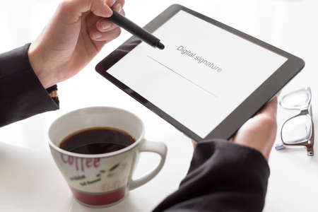 autograph: Hands with tablet and coffee signing Stock Photo